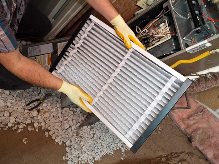 Working on installing a new filter in a new heating system