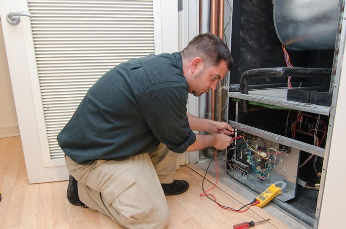 Contractor working on a tuneup for a gas furnace