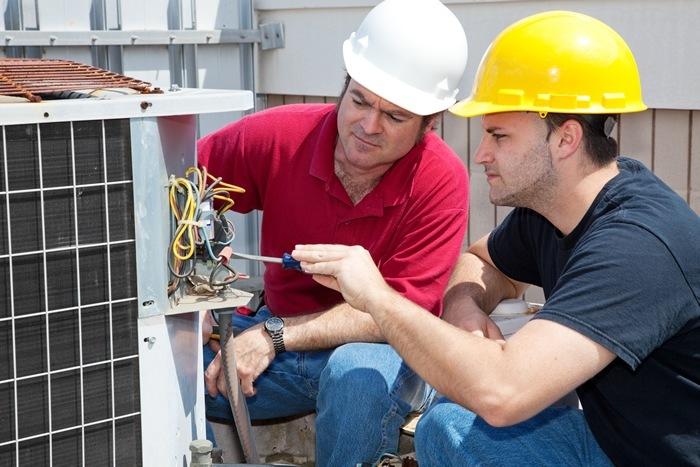 HVAC Technicians repairing a Commercial AC Unit